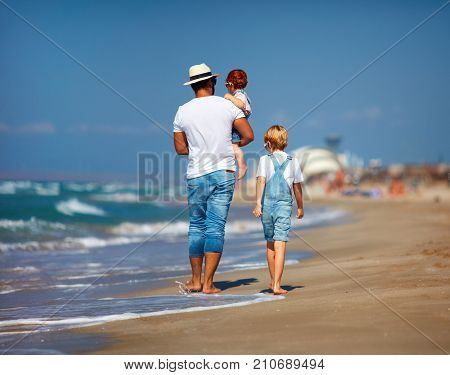 rear view of family father with kids walking on sandy beach near the sea summer vacation