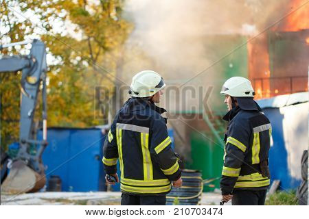 two firefighters stand back on a fire on the background of the fire