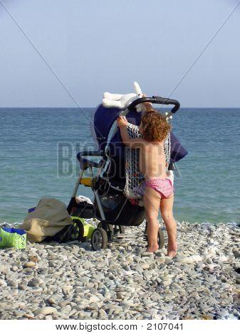 Beach Scene Of Toddler Reaching For Her Teddy Bear