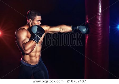 Muscular man boxing punching bag in gym. Power fitness man training hits. Sport fitness boxing concept