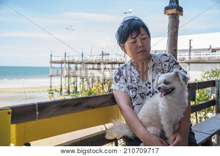 Asian Women And Dog At Beach And Sea When Travel