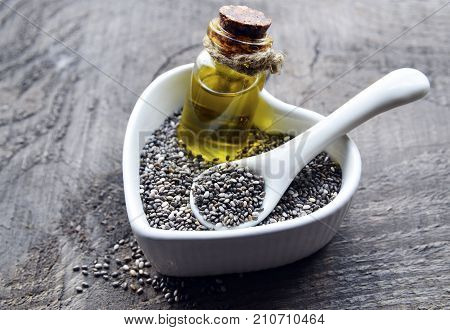 Chia oil with chia seeds in white heart shaped bowl on old wooden background.Organic chia seeds and oil.Healthy food,superfood or bodycare concept.Selective focus.