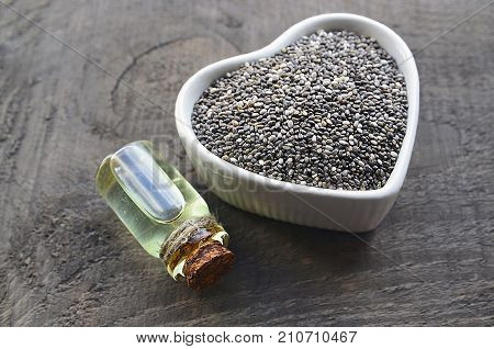 Chia seeds and chia oil on old wooden background.Organic chia seed oil.Salvia hispanica seeds.Healthy food,superfood or bodycare concept.Selective focus.