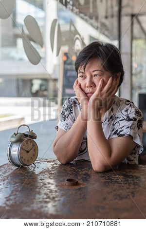 Asian Women Waiting In Coffee Shop Cafe With Clock