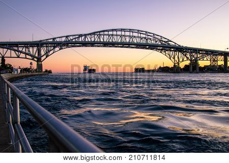 Port Huron, Michigan, USA - October 5, 2017: A freighter travels beneath the twin spans of the Blue Water Bridge international border crossing. The bridge connects Michigan, USA and Ontario, Canada.