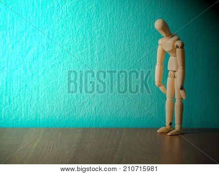 Sad wooden puppet are exhausted and hopeless.Wooden puppet stand on the wooden table. the background is turquoise and copy space for content.