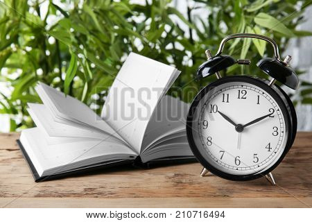 Time management concept. Composition with alarm clock on wooden table
