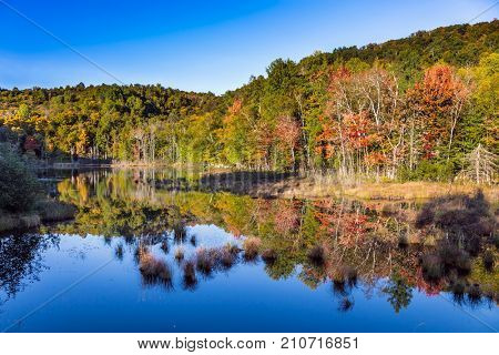 Foliage of autumn forests is reflected in pond. Magnificent resort Mont Tremblant. The pond is smooth like a mirror. Concept of ecological tourism