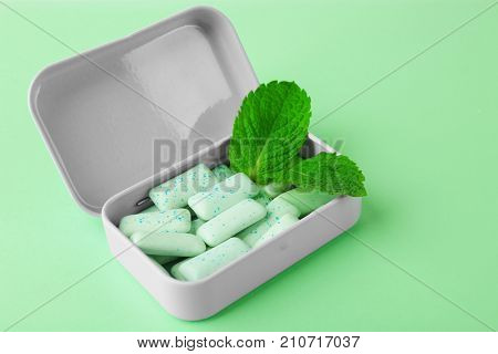 Open box with mint chewing gum on color background