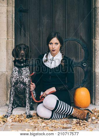 Creepy girl with dog and halloween pumpkin