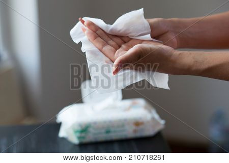 Young woman cleaning hands with wet wipes