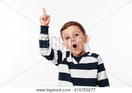 Portrait of an excited smart little kid pointing finger up and looking at camera isolated over white background