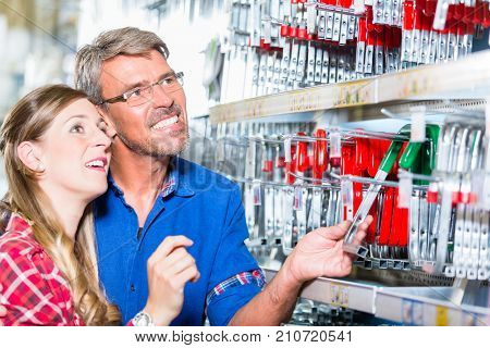 Employee of hardware store helping customer in ironware department with fittings