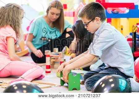 Cute pre-school boy cooperating with his colleagues at the construction of a structure made of wooden toy, blocks under the guidance of a young kindergarten teacher