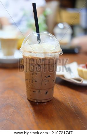 Ice cocoa with whipping cream on wood table
