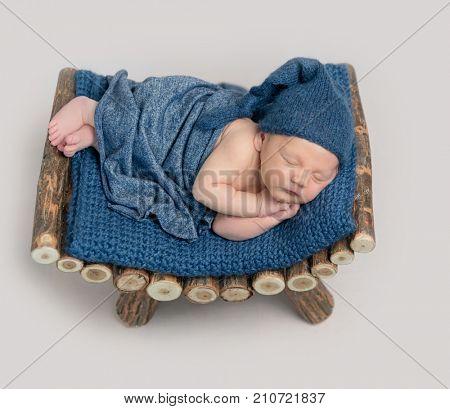Cute boy in blue bonnet sleeping