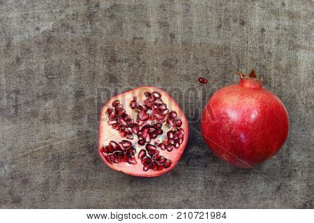 one whole pomegranate (Punica granatum) and a cut half on a grungy metal background