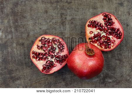 one whole pomegranate (Punica granatum) and two halves on a grungy metal background