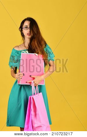 Lady Stands On Yellow Background, Holds Pink Shopping Bags.