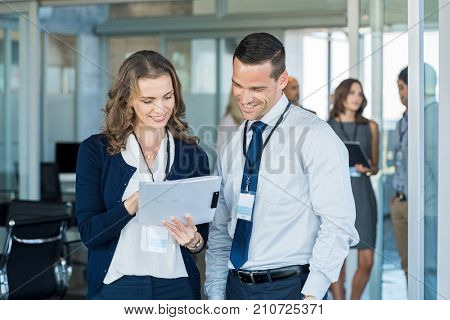 Company employees reading report file at business annual meeting. Manager and smiling businesswoman working together in modern office. Happy businessman and business woman discussing report.
