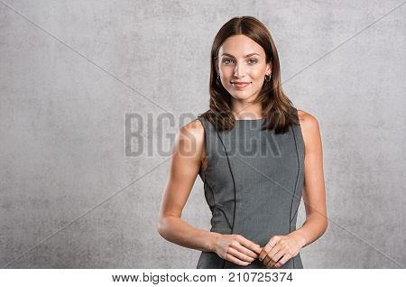 Young business woman feeling confident standing against grey wall with copy space. Portrait of beautiful smiling woman in formal looking at camera. Successful businesswoman on isolated background.