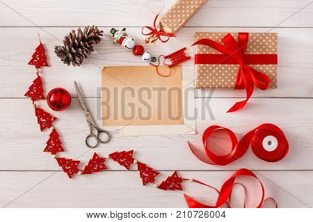Creative diy hobby. Handmade tools for making christmas present, box in craft paper with red ribbon. Top view of white wooden table with copy space on sheet of paper, decoration of gift.