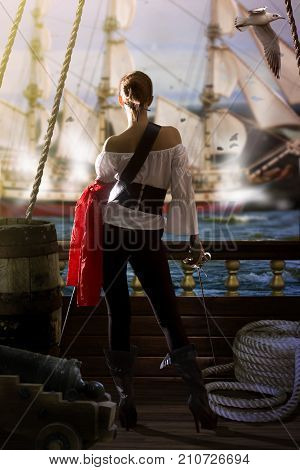 pirate captain in sexy clothes calmly stands on the deck of her ship under enemy fire and waits for an opportunity to attack