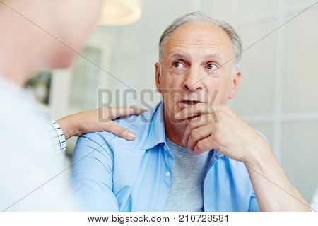 Anxious aged man talking about his worries with friend who cares