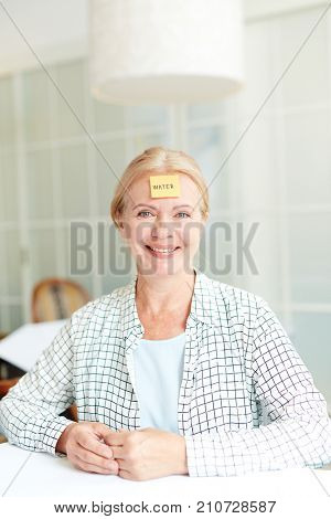 Happy mature female playing leisure game with word water on notepaper stuck to her forehead