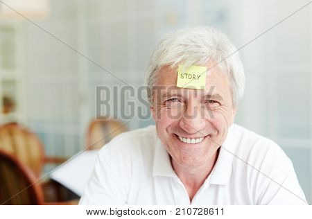 Grey-haired man with notepaper on his forehead should explain or guess the word