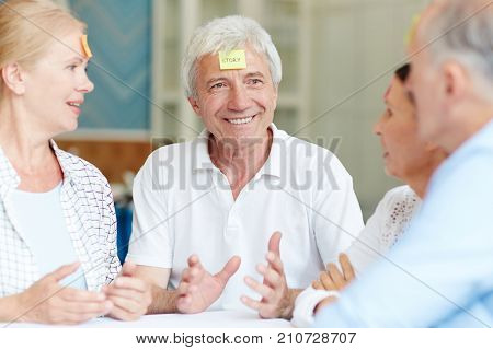 Cheerful senior companions describing what is written on notepapers on their foreheads