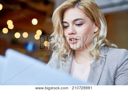 Head and shoulders portrait of attractive blond-haired white collar worker studying documents while sitting at office desk, blurred background