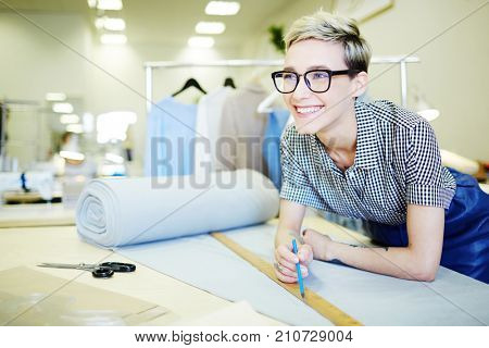 Young shop assistant of sewing department measuring piece of fabric for client