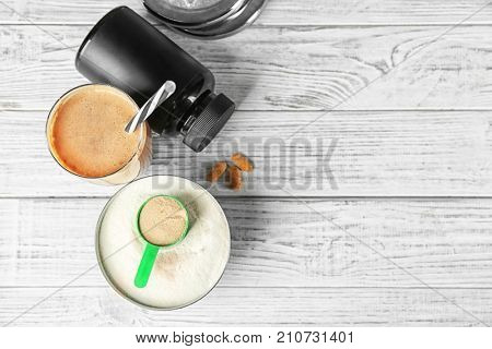 Glass with protein shake and powder on table