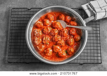 Saucepan with delicious meatballs in sauce on table