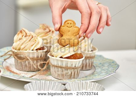 Christmas Treats. Handmade cookies, cupcakes, confection standing on the table.  Female hands decorating cupcakes using gingerbreads. Christmas and New Year.