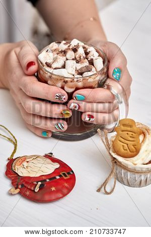 Female hands with bright festive manicure design holding glass mug with hot cocoa and marshmallows. Handmade ginger cookies, cupcake,  confection standing on the table. Christmas and New Year treats.