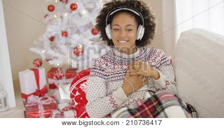 Happy woman enjoying her music at Christmas relaxing on a sofa in front of the tree with a beaming smile clasping her mobile to her chest.
