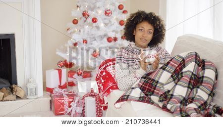 Contented woman in sweater and plaid blanket drinking tea while laying on couch. White Christmas tree with gifts underneath it in background.