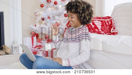 Young woman having a video chat on her laptop waving at the computer as she sits in a red and white themed Christmas living room