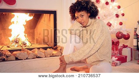 Woman seated by fireplace runs hand in her hair with white christmas tree behind her. She wearing warm woolen winter sweater.