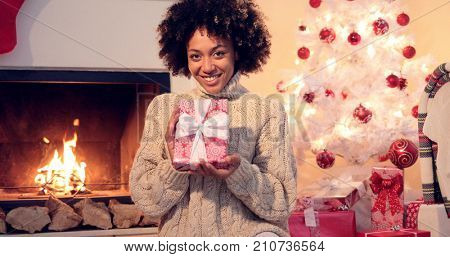 Beautiful african american smiling woman with huge afro haircut  holding xmas boxed gift in hands. She seating next to fireplace and christmas tree.