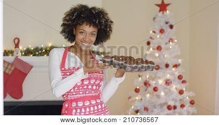 Smiling happy woman in a festive red apron standing in front of the Christmas tree with tray of freshly baked muffins