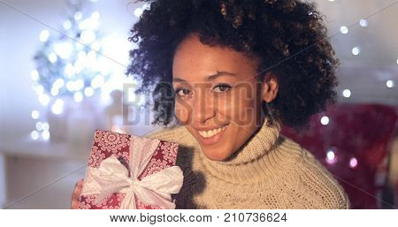 Single beautiful African woman with smile holding Christmas gift wraped with white bow. Includes Christmas tree in background.
