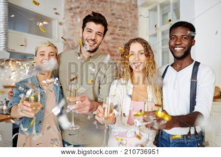 Cheerful couples celebrating holiday and toasting with champagne at party
