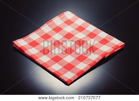 checked napkin cloth at glossy black background