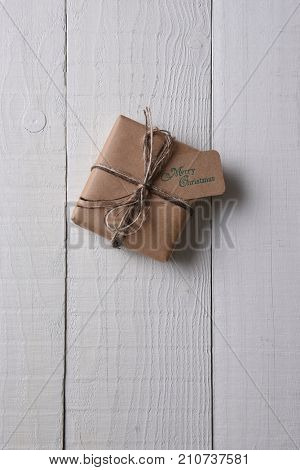 Top view of a single plain paper wrapped Christmas present with a tag stamped with Merry Christmas.