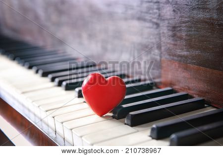 Red heart on piano keys, closeup
