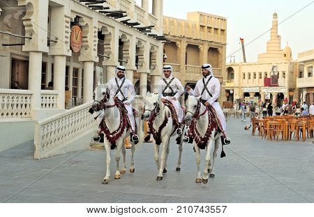DOHA, QATAR - OCTOBER 23, 2017: Mounted police patrol the main thoroughfare of Souq Waqif market in Qatar, Arabia.