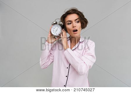 Portrait of a young shocked girl in pajamas holding alarm clock and looking away isolated over gray background